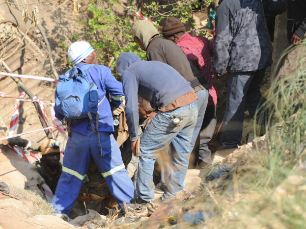 JOHANNESBURG, SOUTH AFRICA – SEPTEMBER 12: Emergency workers and miners team up during a rescue operation of trapped illegal miners at Langlaagte on September 12, 2016 in Johannesburg, South Africa. During the operation, rescue technicians formed a team with illegal miners in search of men trapped underground at the disused mine. One body was recovered.  (Photo by Gallo Images / Beeld / Felix Dlangamandla)