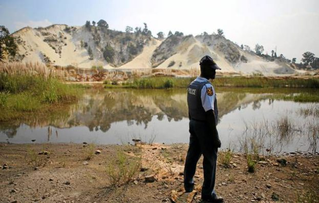 A policeman looks at a mine dump near the scene where eight illegal miners were found dead in Benoni, east of Johannesburg, on Monday.  Image by: ALAISTER RUSSELL